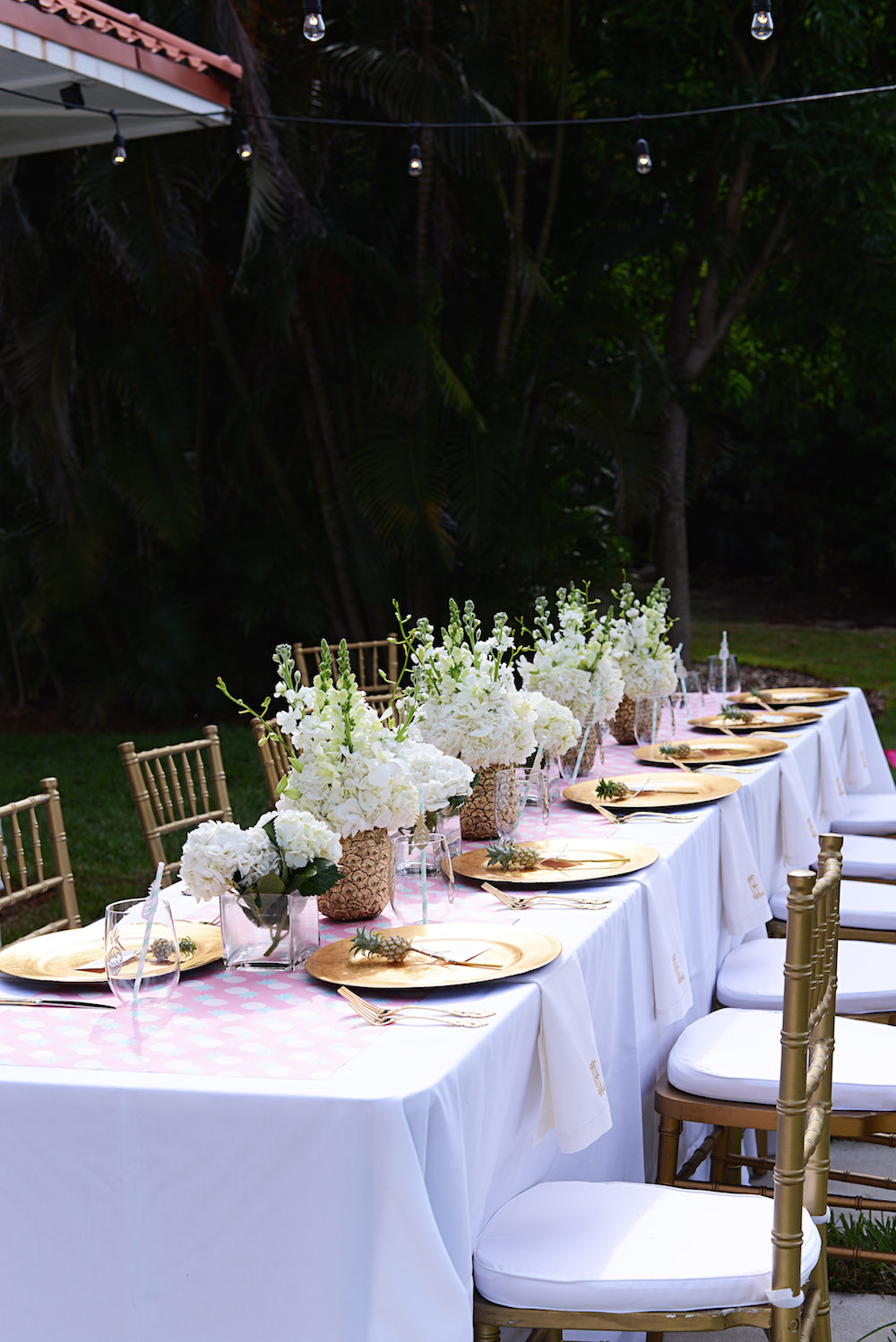 outdoor_dining_pink_table_pineapple_flowers_gold_plate